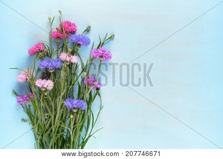 Cornflowers on blue wooden background top view