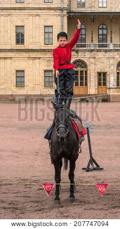 Gatchina St. Petersburg Russia - September 30 2017: Horse show of Cossacks on the parade ground of the Gatchina Palace. A Cossack boy stands on a horse.