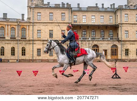 Gatchina St. Petersburg Russia - September 30 2017: Horse show of Cossacks on the parade ground of the Gatchina Palace. The Cossack is juggling a sword.