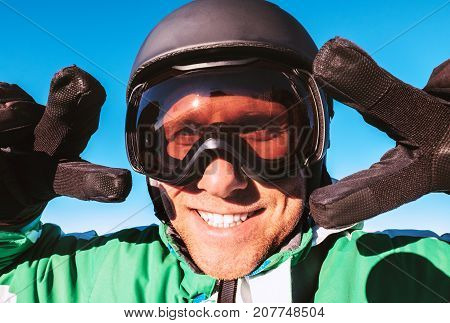 Skier dressed in ski helmet and ski goggles showing the two
