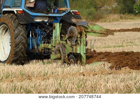 Rear view of old blue tractor ploughing a field with green plough