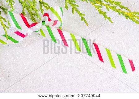 White, Red And Green Striped Silk Ribbon Tied In A Bow On A White Glitter Snow Background