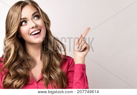 Woman in pink shirt   surprise  points to the top. Beautiful girl  with curly hair surprised and with a smile  looking to the side.Presenting your product. Expressive facial expressions