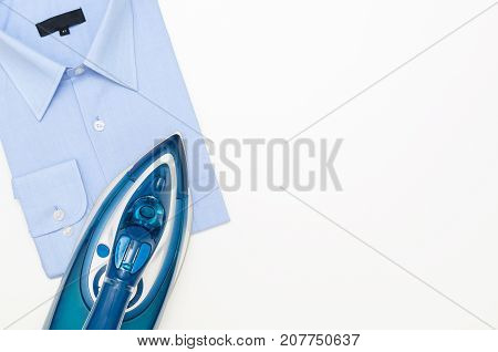 Blue iron and shirt on ironing board top view. iron board clothes ironing shirt household appliance electric concept