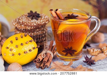 Autumn hot tea with lemon and spices in glass cup. Healthy tea with cookies wal nuts and leaves around. Fall concept