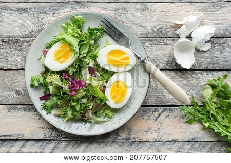 Vegetable salad with sliced boiled eggs and fresh lettuce and rucola served on wooden table. Top view.