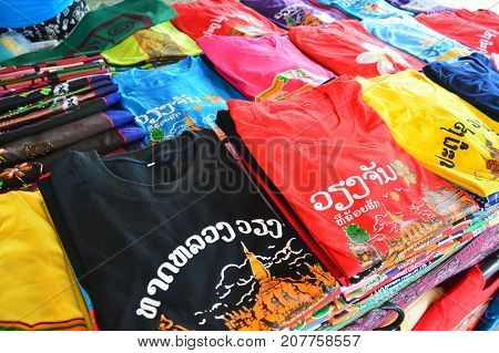 Vientiane, Laos - August 2015: Colorful t-shirts with Lao tourist attractions screen printing sold at souvenir shop in Vientiane capital city of Lao PDR. Lao texts translated as