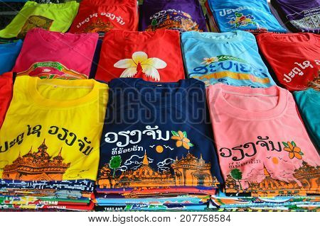 "Vientiane, Laos - August 2015: Colorful t-shirts with Lao tourist attractions screen printing sold at souvenir shop in Vientiane capital city of Lao PDR. Lao texts translated as ""Sabaidee (Lao greetings)"" ""Patuxay Vientiane"" and ""I Love Vientiane"""