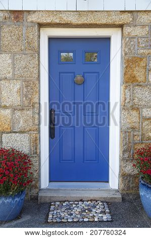 residence front entrance. sleek design. blue door with door knocker, stone doormat and potted plants. Vertical