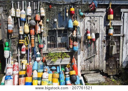 fishing wooden house with nets and buoys. colorful lobster buoys and fishnets hanged on wooden wall