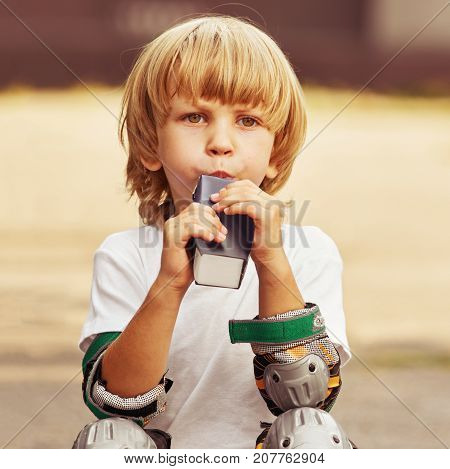 Portrait of little boy roller skater drinking juice, image with toning