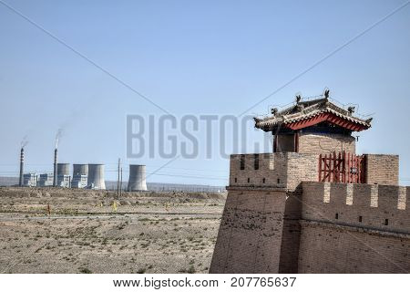 The Watchtower on the Jiayu Pass, the first pass at the west end of the Great Wall of China, near the city of Jiayuguan in Gansu province in China with power station and stalk in the background.