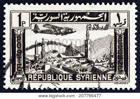 SYRIA - CIRCA 1937: A stamp printed in Syria shows airplane over Damascus, circa 1937.