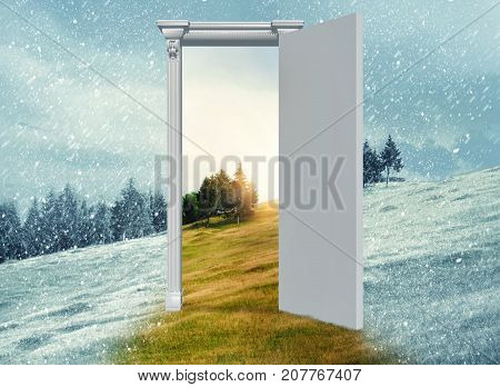 Opened door on a field during winter which leads to a warmer season. Changing season through the door concept.