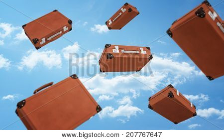 3d rendering of a several brown retro suitcases closed with buckles flying on cloudy sky background. Travelling and adventures. Luggage and bags. Necessities at hand.