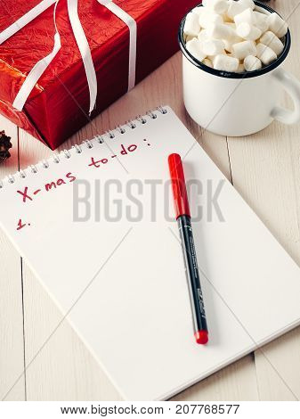 Christmas to-do list. Xmas gifts shopping planning. Make shopping or to-do list for Christmas. Notebook, mug hot chocolate with marshmallows and New Year's gift on white wooden background.