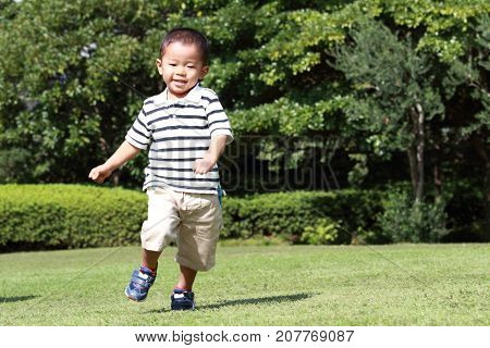 Japanese Boy Running On The Grass (3 Years Old) In Summer