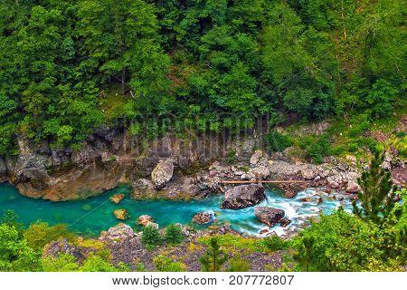 Mountain river flows in the canyon skirting large boulders. Tara River Canyon. Durmitor National Park. Montenegro.