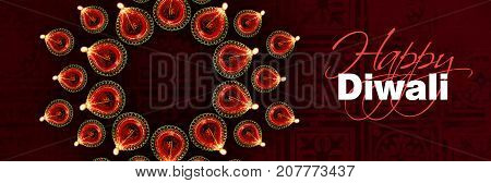Stock photo of diwali greeting card showing top view of illuminated diya or oil lamp or panti forming a design or rangoli copy space and with Happy Diwali text