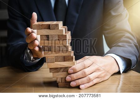 Alternative risk concept plan and strategy in business Young intelligent businessman raise the wood game hands of executive sustain wood block on the tower Collaborative management.