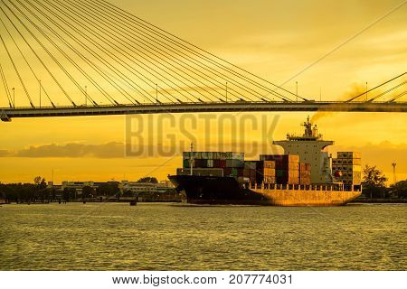 Container cargo ocean ship float on river and pass under bridge at sunset twilight with red sky
