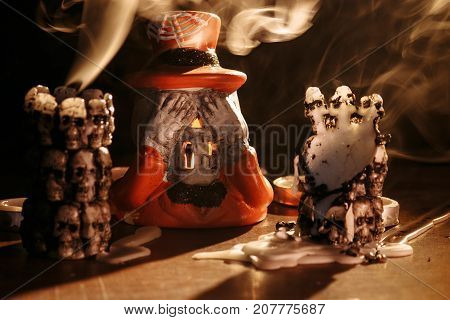 smoke from extinct candles has filled space and has shrouded a candlestick in the form of the skeleton dressed in a dress coat and a hat.