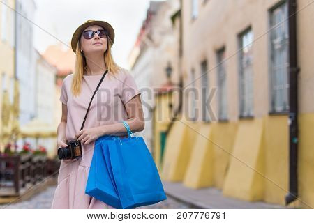 Travel And Shopping Concept - Happy Woman Tourist Walking In City With Shopping Bags