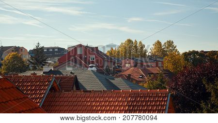 Autumn landscape of a small Balkan town just colorful trees and roofs.