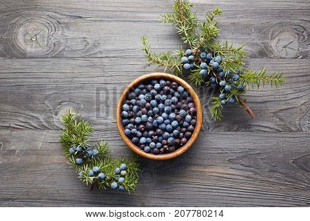 Wooden bowl with seeds of juniper. Juniper branch with berries. Juniper berries in a bowl with a sprig.