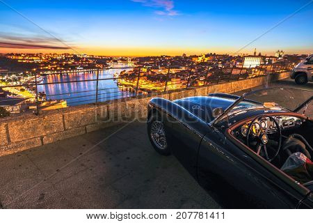Porto, Portugal - August 11, 2017: luxury car parking at Miradouro da Serra do Pilar in Vila Nova de Gaia. Scenic skyline on Douro River and Ribeira waterfront at twilight.Luxury concept and lifestyle