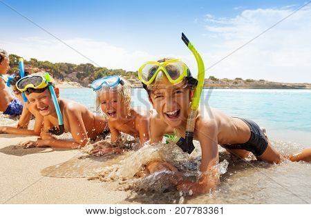 Group of kids in scuba gear on the beach with wave and water flush them laughing smiling