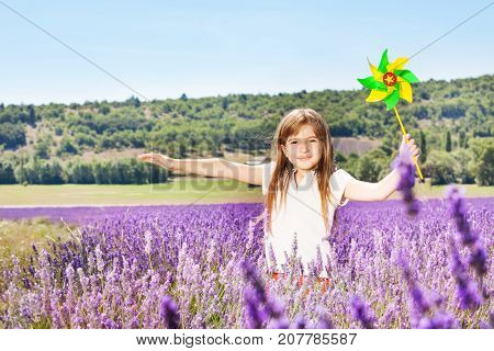 Portrait of beautiful preteen girl playing with colorful pinwheel in lavender field in summer