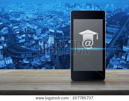 E-learning icon on modern smart phone screen on wooden table over city tower street and expressway Study online concept