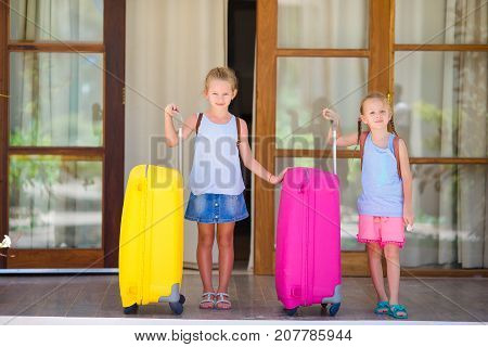 Little tourists girls with big luggages on their traveling