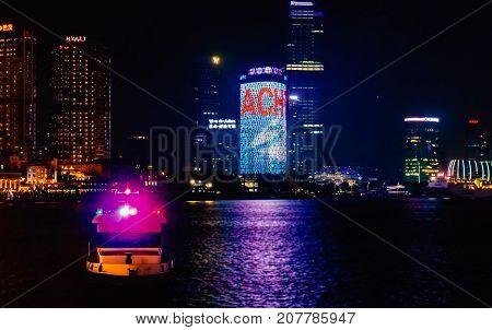 Shanghai, China - Nov 4, 2016: Shanghai City skyline by night at The Bund. Features the shoreline and Huangpu River. Available-light image. Some low-lying fog moving in.