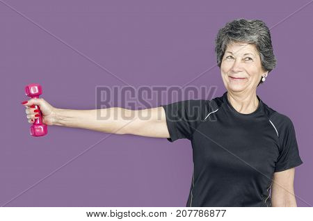 Senior woman in a gym class doing Pilates exercise lift weights over a purple background