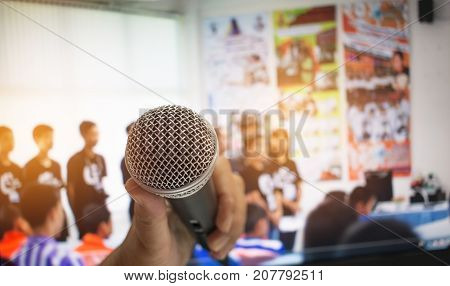 Hand holding Microphone on abstract blurred of front podium and speech in seminar room speaking conference room Concept of Speech and speaking.