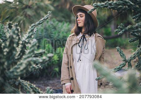 Happy brunette woman walks garden fool of wild desert cacti in old fashioned wedding white dress and brown hat