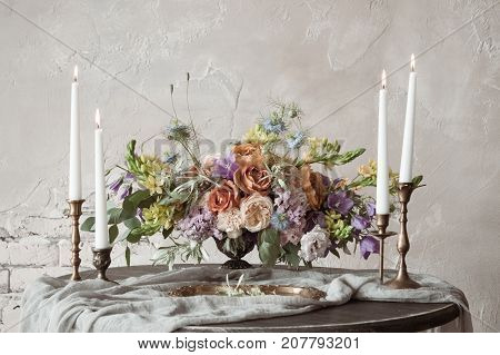 Analog film styled photo of beautiful wedding composition of roses in pastel shades with candles in vintage candlesticks