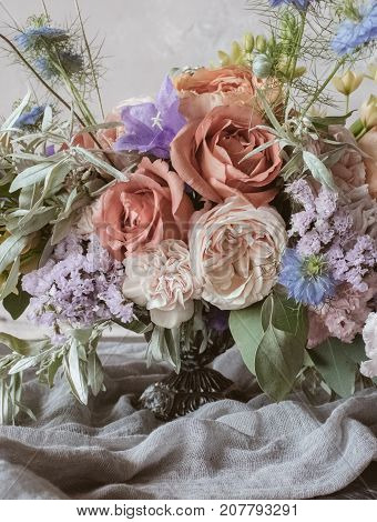 Analog film styled photo of beautiful wedding bouquet of roses in pastel shades with handcrafted textile