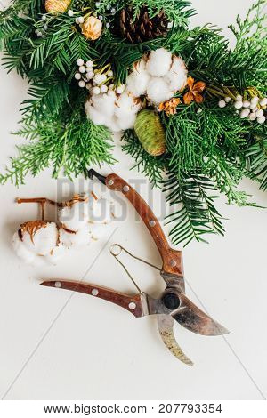 Christmas handmade wreath with coniferous branches cotton flowers silver brunia and leucadendron and secateurs on white wooden table background