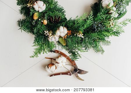 Christmas handmade wreath with coniferous branches cotton flowers silver brunia and leucadendron and secateurs on white table