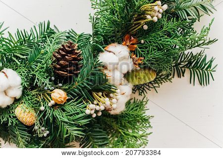 Christmas handmade wreath with coniferous branches cotton flowers silver brunia and leucadendron on white table close up view
