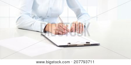 Woman's hands writing on sheet in a clipboard with a pen isolated on desk