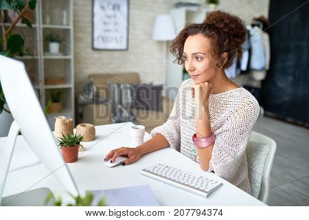 Portrait of smiling mixed-race woman enjoying work from home in modern apartment sitting at desk with computer