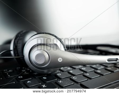 Closeup headset on laptop computer keyboard in monotone with selective focus (Communication concept)