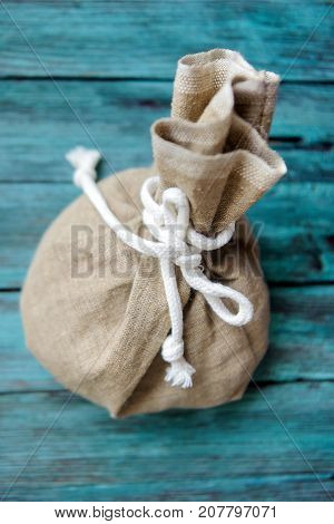 sack with coins on a beautiful wooden background