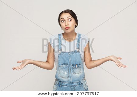 Negative Human Emotions, Facial Expressions. Puzzled  Young Adult Woman With Arms Out, Shrugging Her