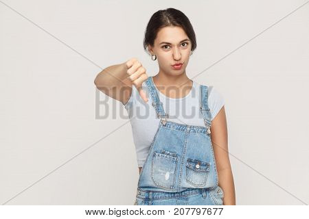 Young Adult Woman Showing Thumb Down Isolated On A Gray Background. .