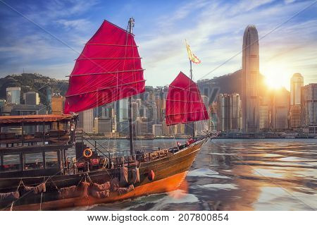 Vintage sail boat fron victoria port to Hongkong harbour for survice to tourist in Hong kong coty with sunset and blue sky China Travel asia and cityscape concept